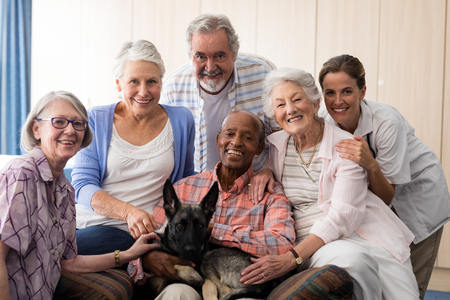Portrait of smiling doctor and senior friends with dog at nursing home Banco de Imagens