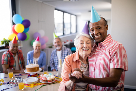Portrait of senior couple standing by table during birthday party with friends in background Stock Photo