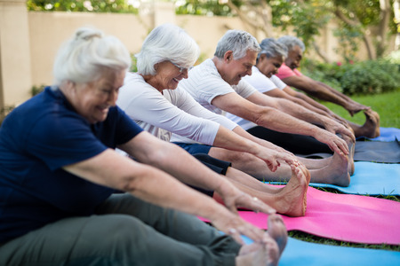 Smiling multi-ethnic senior people doing stretching exercise while sitting on exercise mats at park