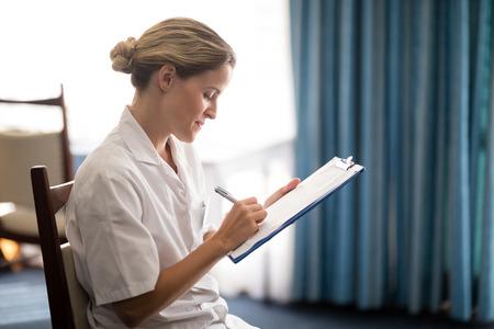 Zijaanzicht van jonge vrouwelijke arts die op klembord bij pensioneringshuis schrijft