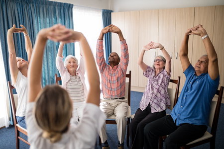 Female doctor stretching with seniors sitting on chairs at retirement home Stock Photo
