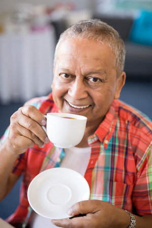 Portrait of smiling senior man drinking coffee while sitting in nursing home