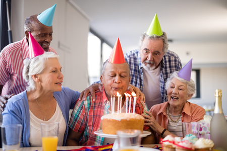 Friends looking at senior man blowing candles on birthday cake during party in nursing home