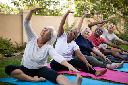 Senior people with arms raised exercising while looking up at park