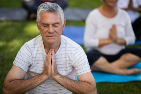 closed community: Senior man with eyes closed meditating in prayer position while sitting with friends at park Stock Photo