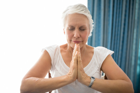 Senior woman praying with eyes closed against window at retirement home Stock Photo