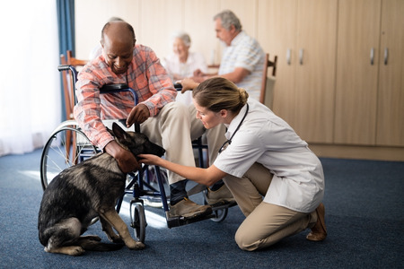 Female doctor kneeling by disabled senior man stroking puppy at retirement home