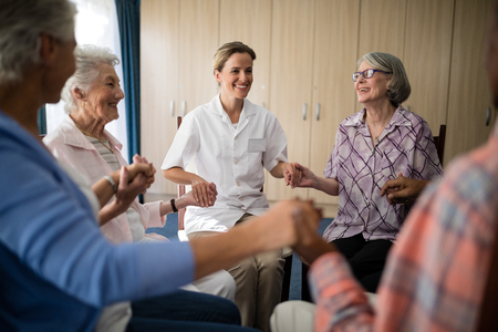 closed community: Smiling female doctor holding hands with seniors while sitting on chairs at retirement home Stock Photo