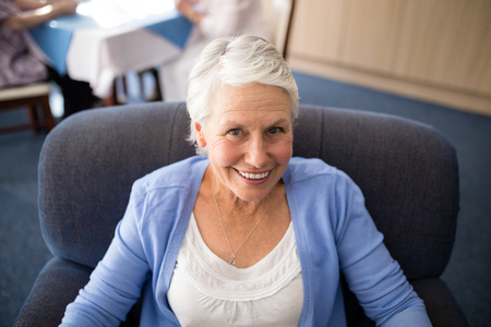 High angle view of smiling senior woman sitting on armchair at retirement home