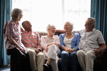Smiling senior friends talking while sitting on couch against window in nursing home