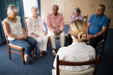 Rear view of female doctor meditating with senior people at retirement home