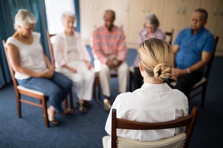 女性医師老人ホームで高齢者と瞑想の背面図