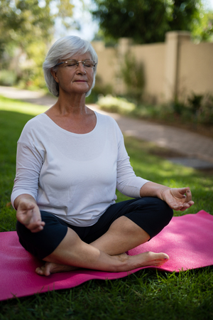 Full length of senior woman meditating while sitting on exercise mat at park