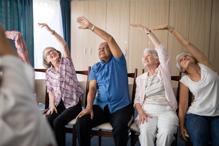 Smiling senior people stretching with female doctor at retirement home