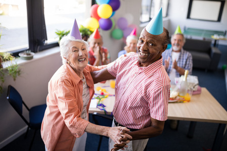 Portrait of happy senior couple dancing by table at birthday party