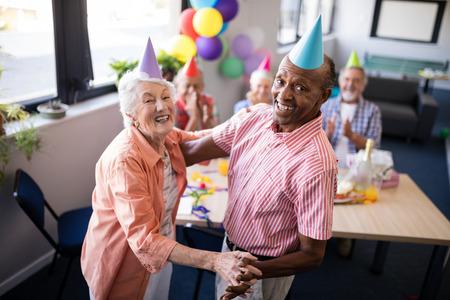 Retrato de feliz pareja senior bailando junto a la mesa en la fiesta de cumpleaños Foto de archivo - 82720490