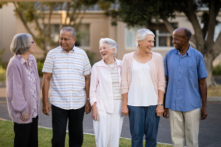 Cheerful seniors standing while looking at each other against retirement home