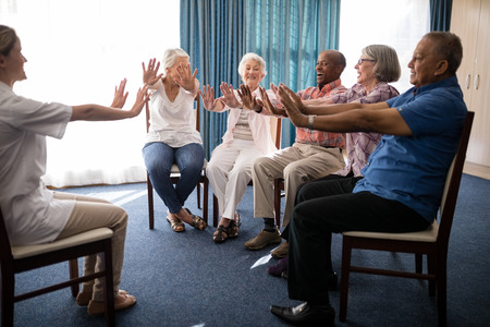 Female doctor and seniors exercising on chairs at retirement home Stock Photo