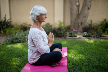 closed community: Side view of senior woman meditating in prayer position at park Stock Photo