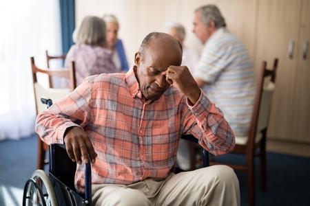 Depressed disabled senior man sitting on wheelchair at retirement home