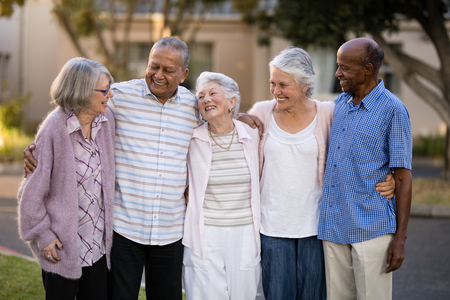 Smiling senior friends standing with arms around outside nursing home 스톡 콘텐츠