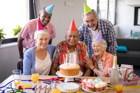 Portrait of cheerful senior people celebrating birthday at nursing home Stock Photo