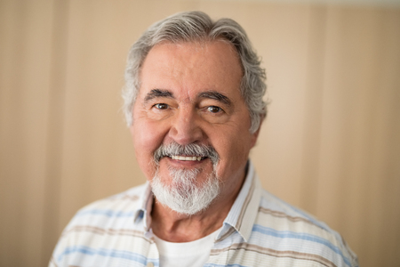 Close-up portrait of senior man against wall at retirement home
