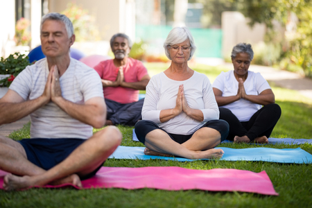 closed community: Senior people with closed eyes meditating in prayer position while sitting on exercise mats at park