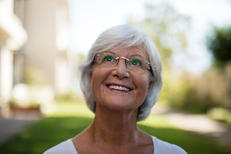 Close-up of thoughtful smiling senior woman wearing eyeglasses at park