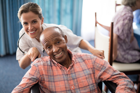 Portrait of cheerful female doctor standing with disabled senior man on wheelchair at retirement home