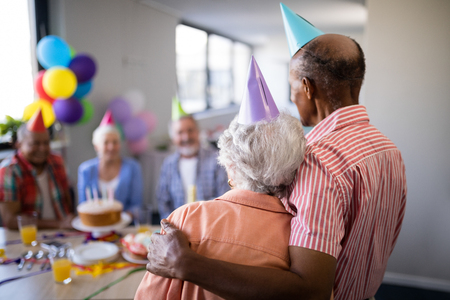 Rear view of senior couple looking at friends sitting by table during birthday celebration Stock Photo