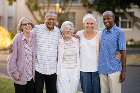 Portrait of cheerful senior people standing with arms around outside nursing home Stockfoto
