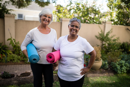 Portrait of smiling senior friends carrying exercise mats while standing at park Standard-Bild
