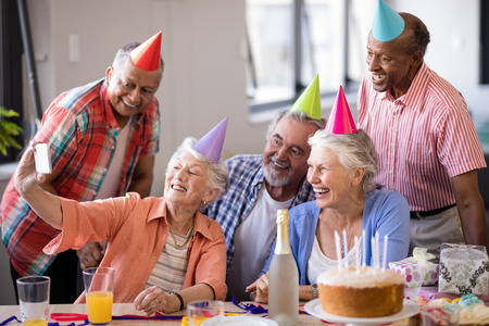 Smiling senior people taking selfie through mobile phone at birthday party