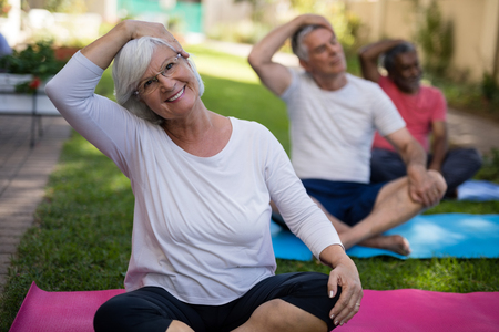 Smiling senior woman stretching head while exercising with friends at park