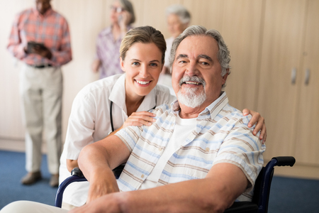 Portrait of smiling female doctor with disabled senior man sitting on wheelchair at retirement home Archivio Fotografico