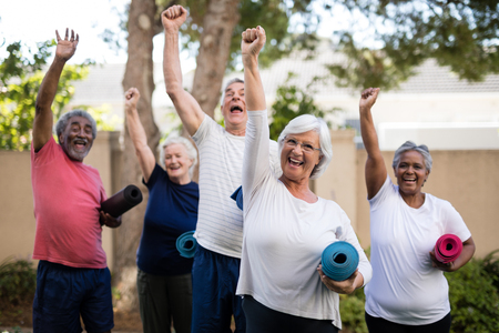 nursing class: Cheerful multi-ethnic seniors with arms raised carrying exercise mats at park