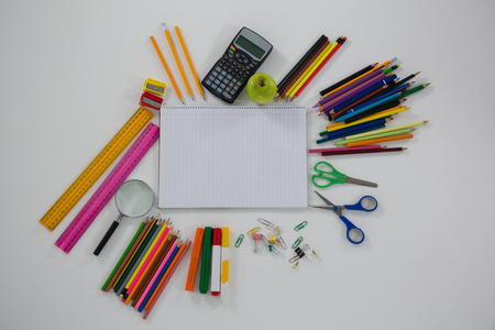 Overhead view of various school supplies arranged on white background