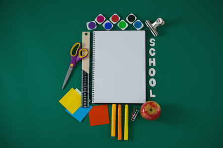 Overhead view of school supplies with text arranged on green background Stock Photo