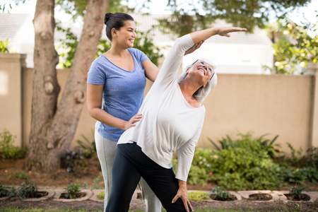 Smiling trainer instructing senior woman while exercising at park
