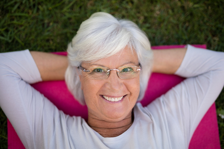 nursing class: High angle portrait of smiling senior woman lying on exercise mat at park
