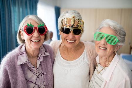 Portrait der lächelnden älteren Frauen, die Neuheitsgläser im Pflegeheim tragen