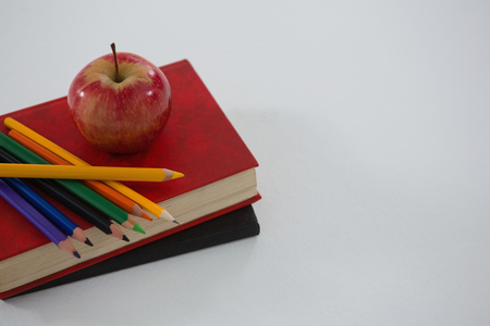 living wisdom: Apple and color pencil on book on white background