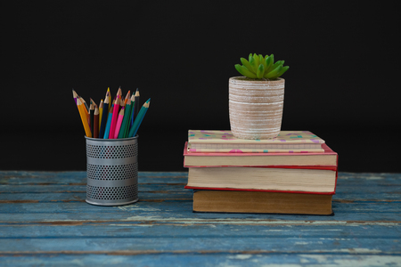 living wisdom: Pot plant, color pencils and book stack on wooden table against black background