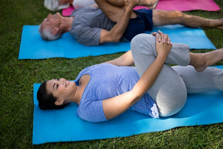 Smiling trainer exercising while lying down with senior people at par