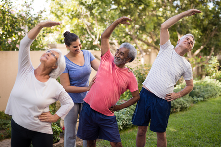 Trainer assisting senior people while exercising at park Stock Photo