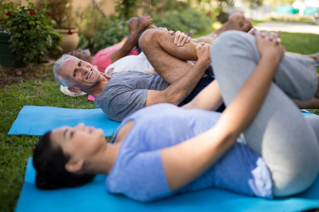 Smiling senior man exercising while lying down by trainer and friends at park