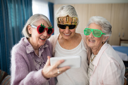 Senior women wearing novelty glasses taking selfie through smart phone at nursing home Foto de archivo