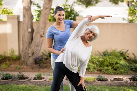 Portrait of smiling trainer assisting senior woman while exercising at park