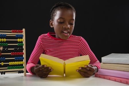 Attentive schoolgirl reading a book against black background Stock Photo